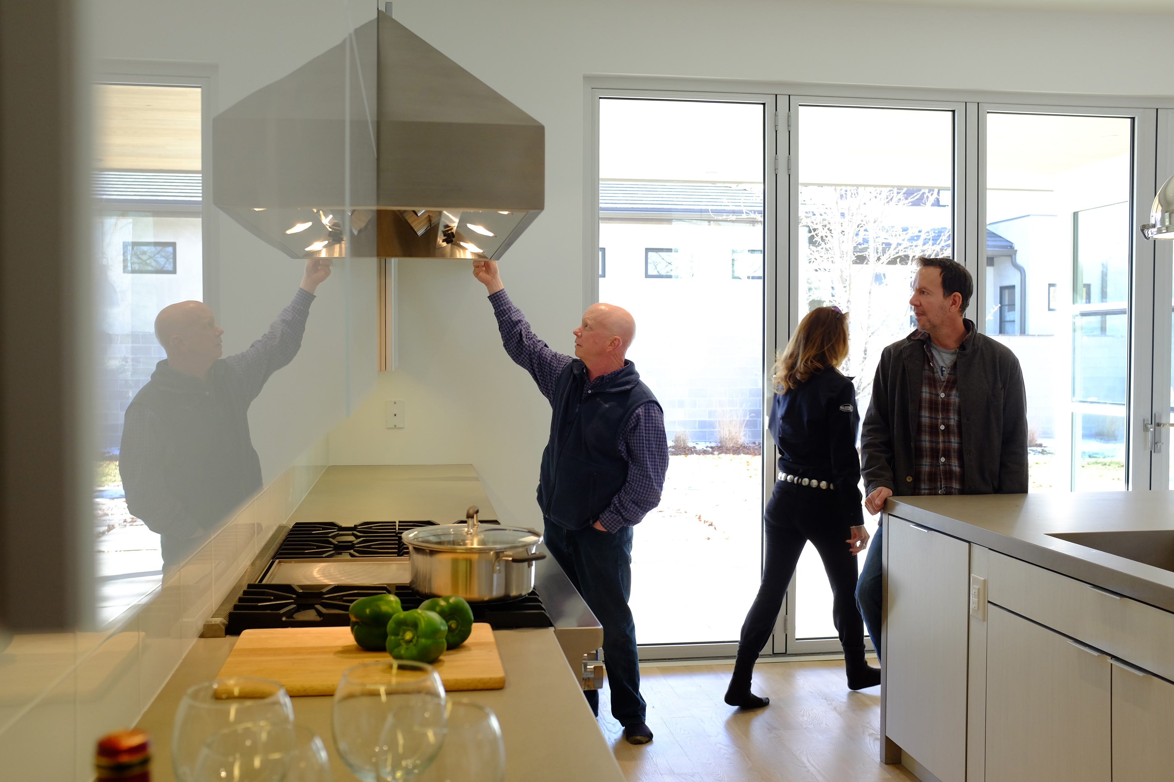Three adults looking around the kitchen of a home for sale.
