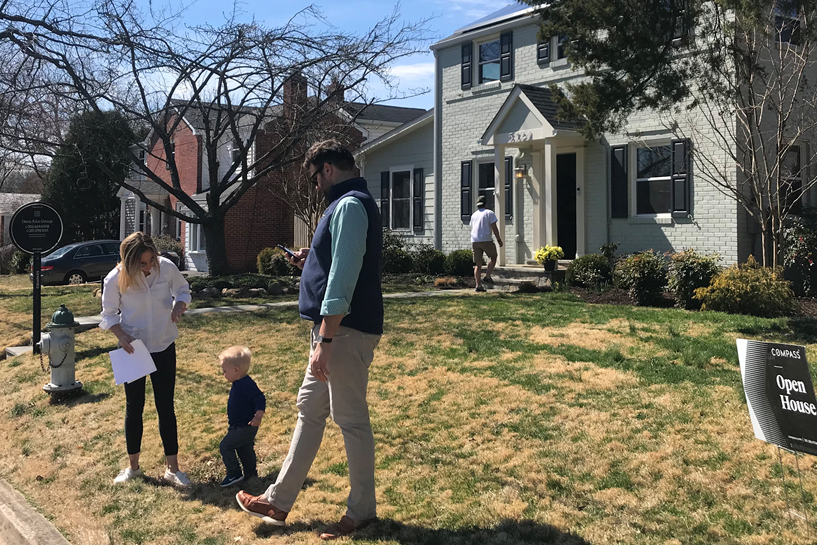 Husband, Wife and child standing in front of an Open House while another man is getting ready to enter the open house.