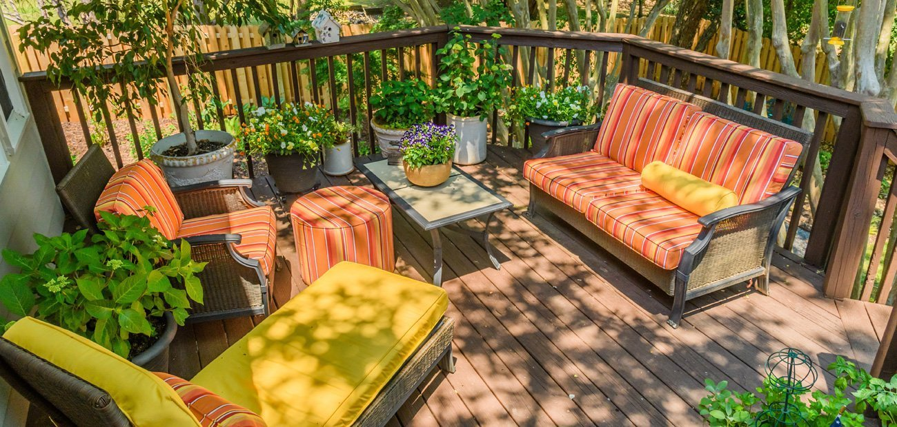 Backyard wooden deck with furniture and colorful coverings and plants