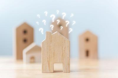 Depiction of frame of a wood home with question marks over the home. More wooden homes sit in the background slightly blurred.