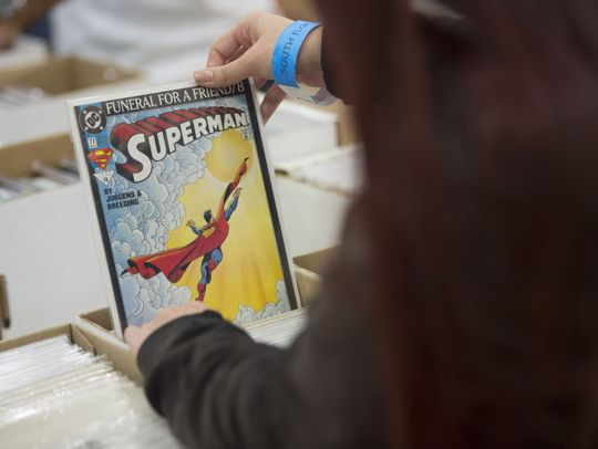 A person holding an Original Superman Comic book at Free Comic Book Day.