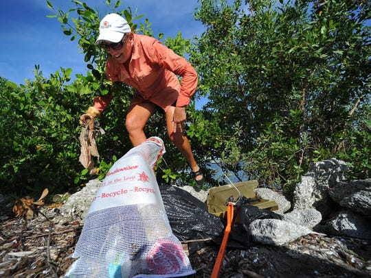 A person participating in the Treasure Coast Waterway Clean Up and picking up trash