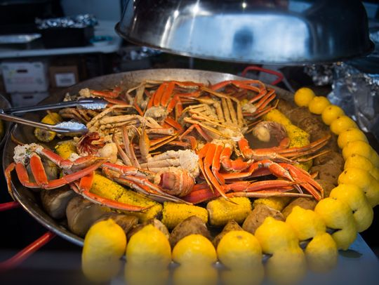 Pan full of steamed crab legs, potatoes, corn on the cobb and lemon wedges.