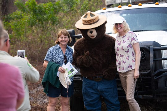 A man taking a picture of 2 women standing next to Smokey the Bear