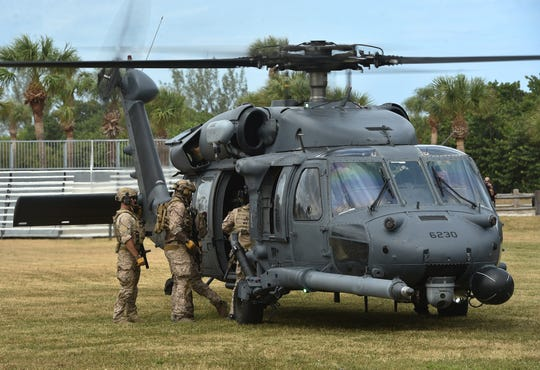 Army helicopter with 3 Navy Seals getting in.