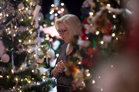 A woman admiring beautiful decorated and lighted Christmas trees