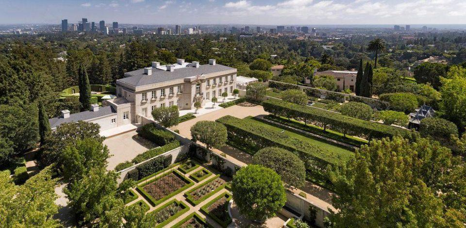 Arial picture of a mansion and the extensive landscaping and gardens around it, with the city scape in the background.