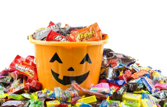 Orange pail with a pumpkin face filled with candy and candy lying all around the pail.