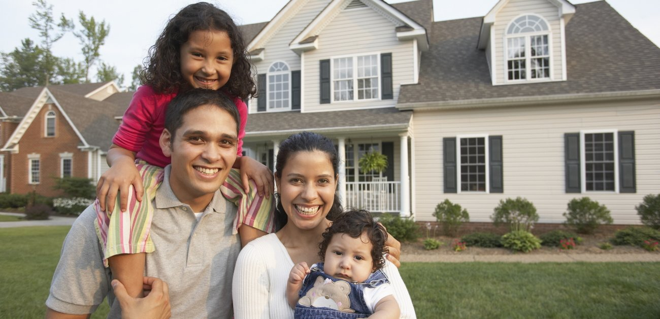 A Hispanic couple pose with their children in front of their new home to represent fair housing enforcement