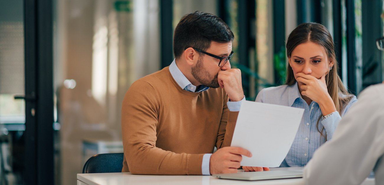 A man and a woman sitting at a table reviewing a contract for selling their home represent What if Your Sellers Have Nowhere to Go.