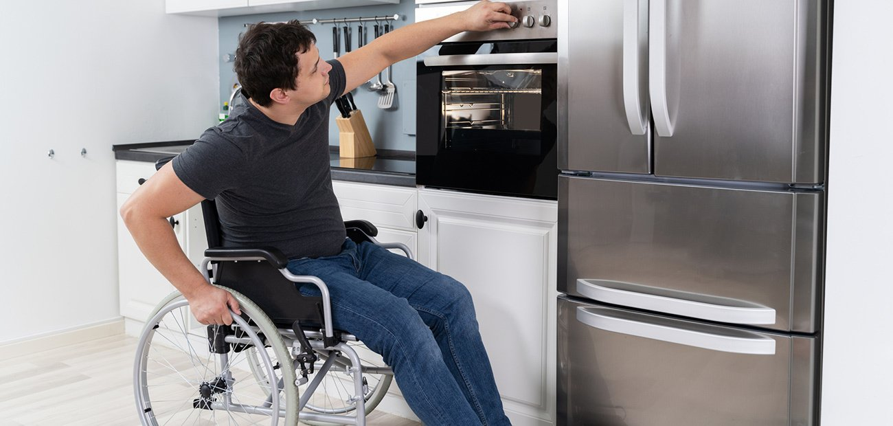 A man in a wheel chair in his his kitchen demonstrating Growing Accessibility Challenges