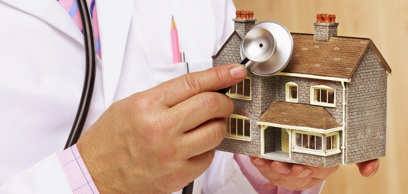 A person posing as a Doctor holding stethoscope to model house, mid section