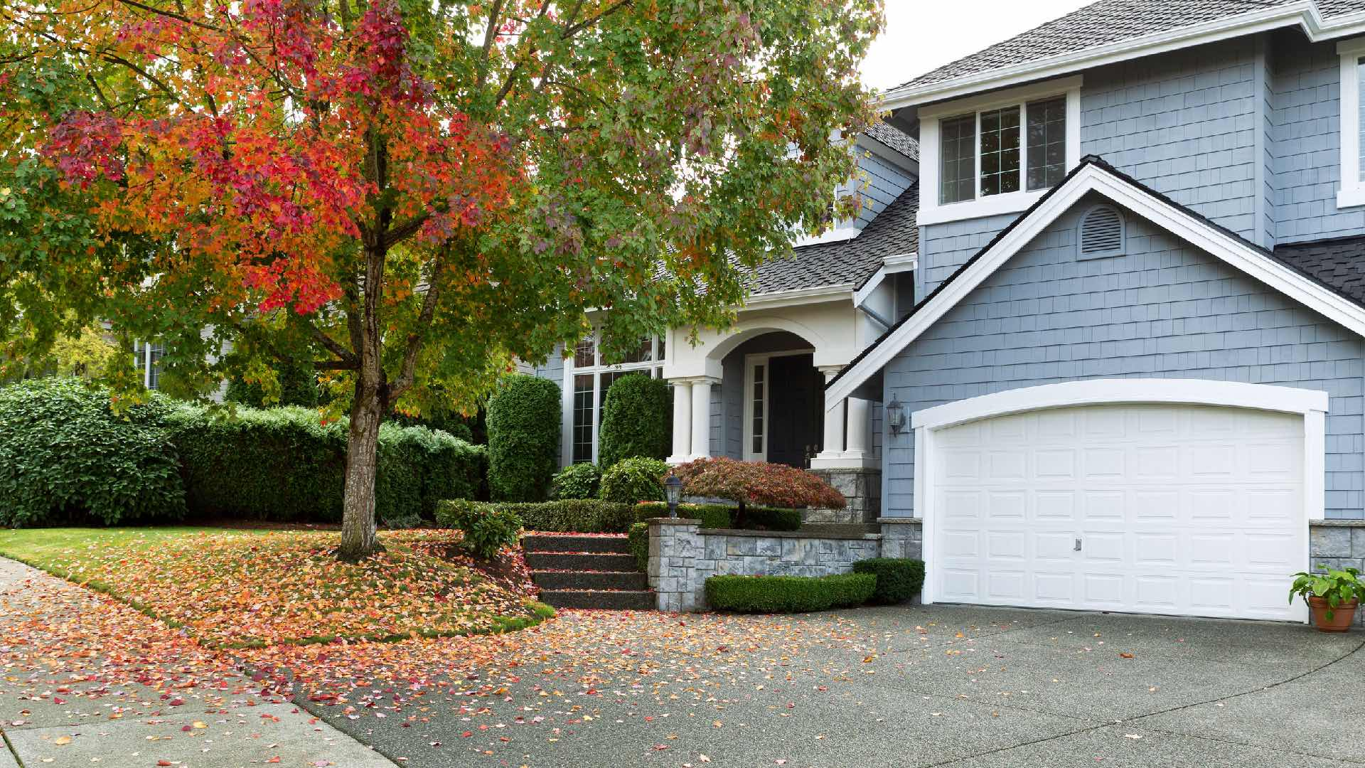 Photograph of a multi-level home with a autumn tree with leaves changing colors