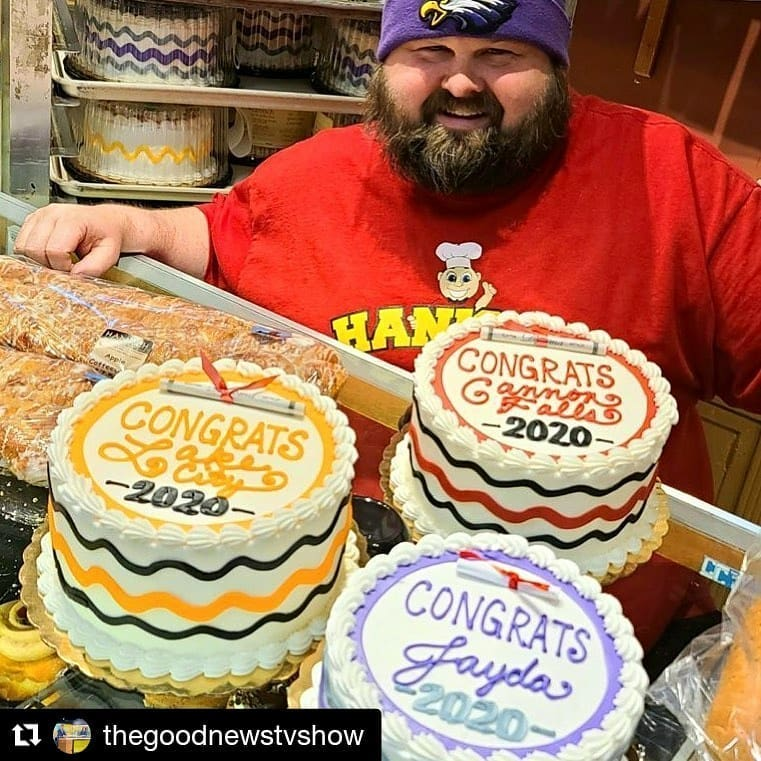 Photo of Bill Hanisch, the owner of Hanisch Bakery behind his graduation cakes