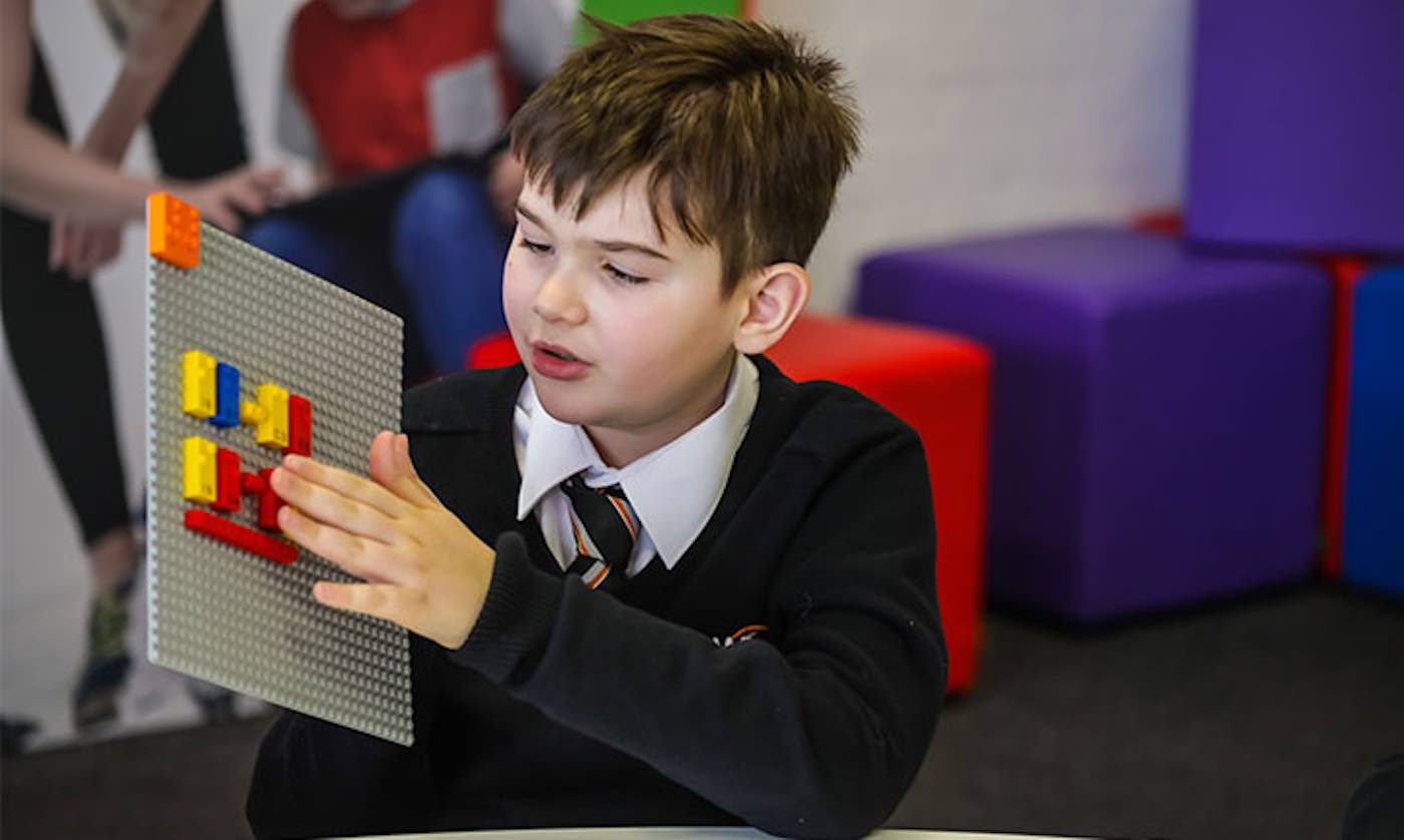 Young boy holding a lego board and putting braille legos on it.