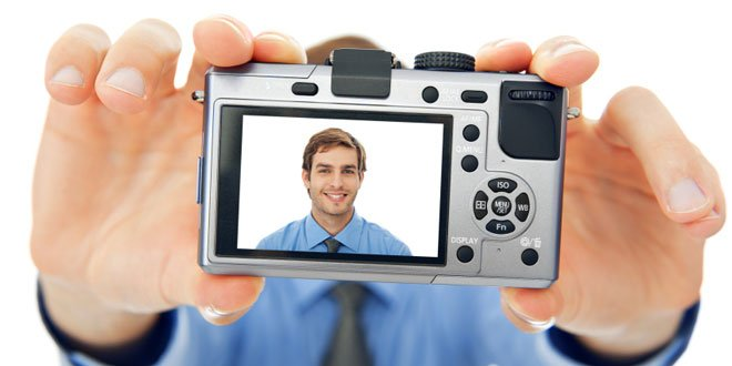 Man holding a camera backwards showing a picture of himself in the camera viewer.
