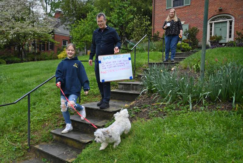 Darcy Schruben, along with her dad, Tom Schruben, and mom, Ann Schruben, make their way to the curb to post the daily bad dad joke on Friday. Michael S. Williamson-The Washington Post