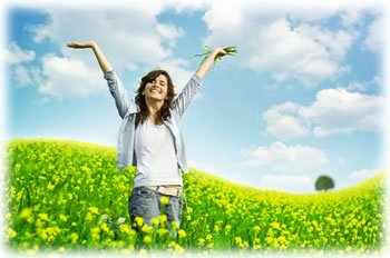 woman standing in a field of flowers with her hands in the air on a beautiful day.