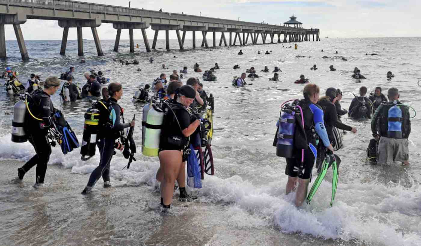 Divers entering and getting ready to enter the ocean to clean up trash on the ocean floor.