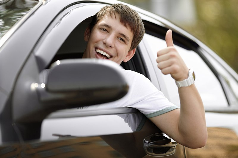 Young man hanging outside the drive side window of his vehicle smiling and giving thumbs up.