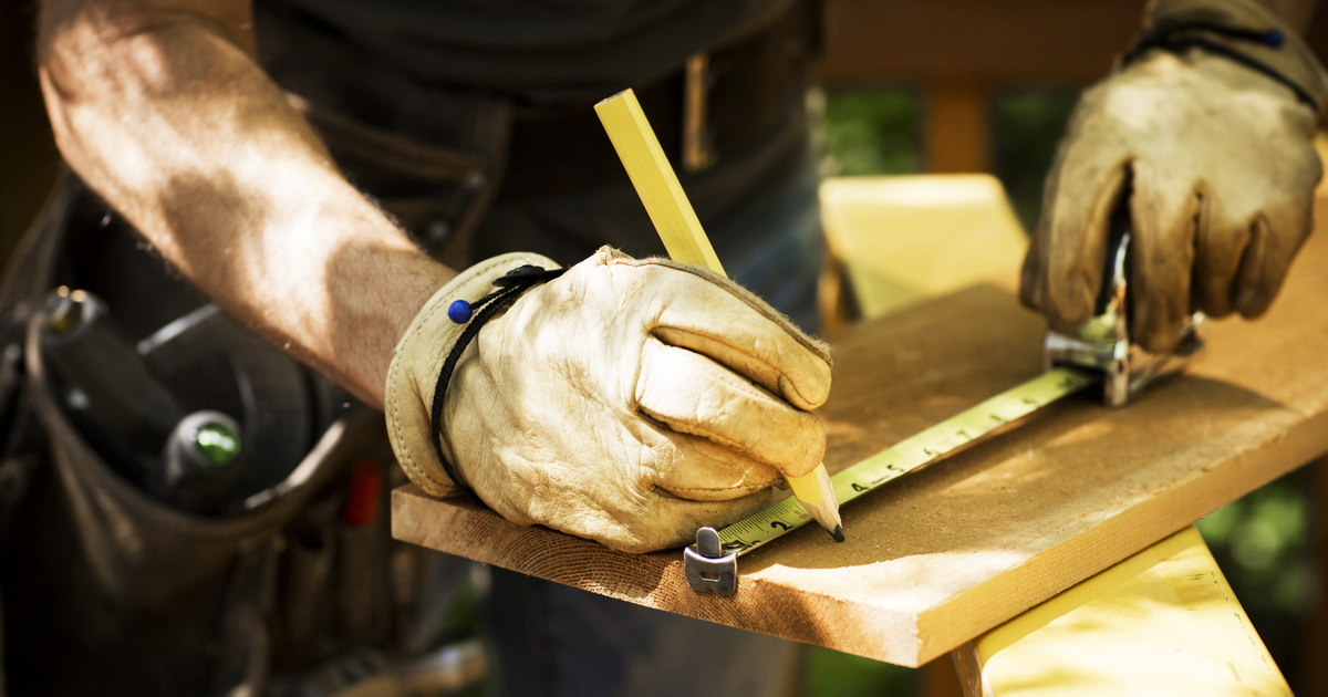 Construction worker using a tape measure to mark a wooden board for cutting.