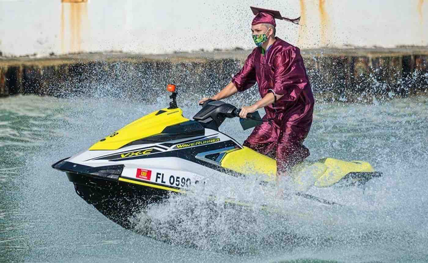 Picture of a young man in Graduation Cap and Gown Riding a jet ski to get his diploma