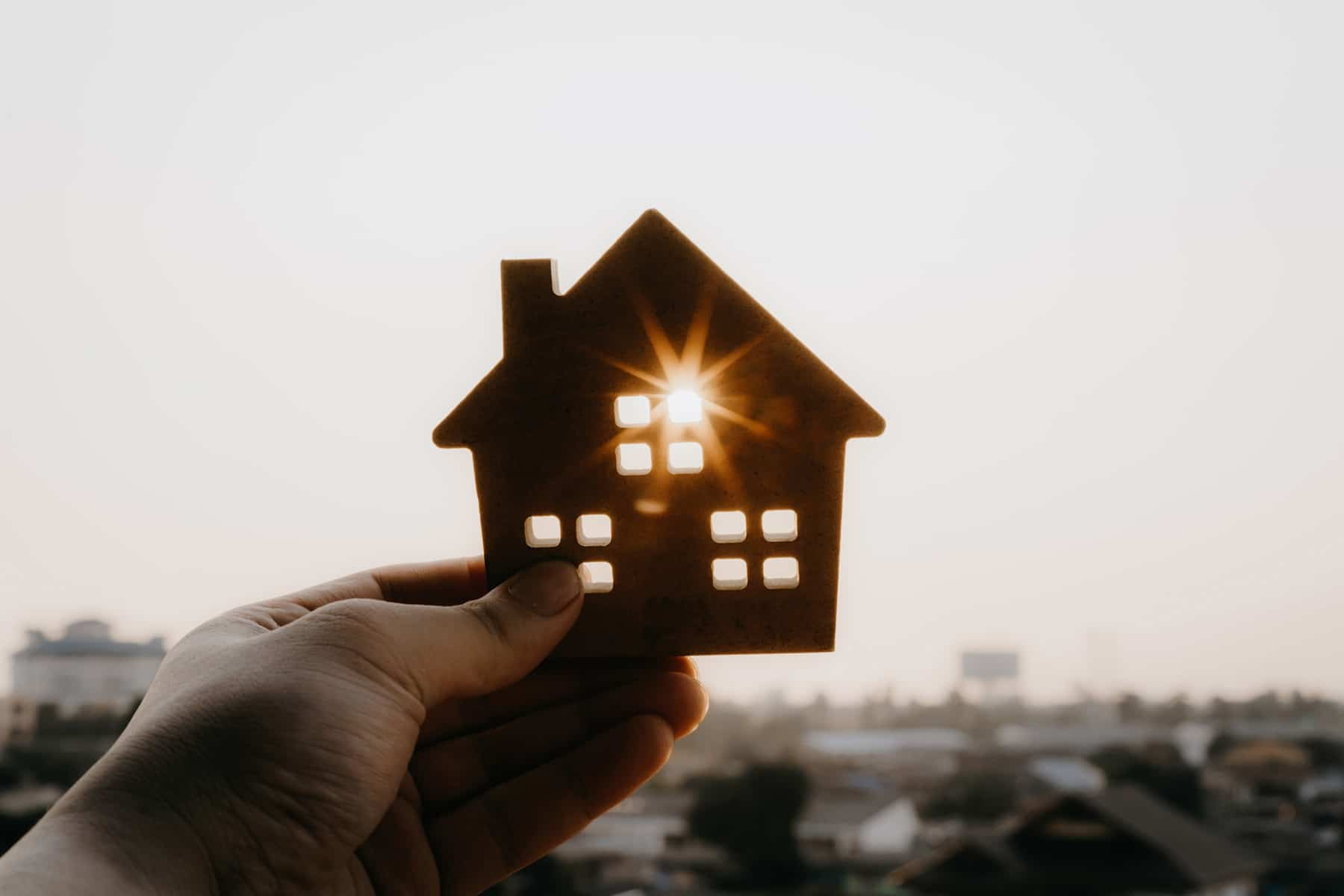 Graphic of a hand holding a cutout house agains the sun to represent affording housing under attack in Florida by the Florida Legislature