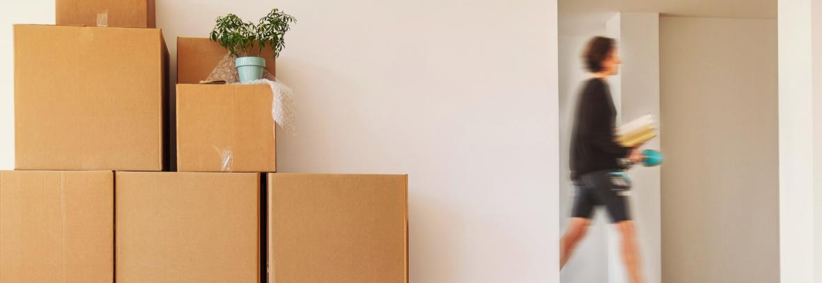 Moving scams are on the rise in Florida. Picture of moving boxes and a blurred person walking in the background.