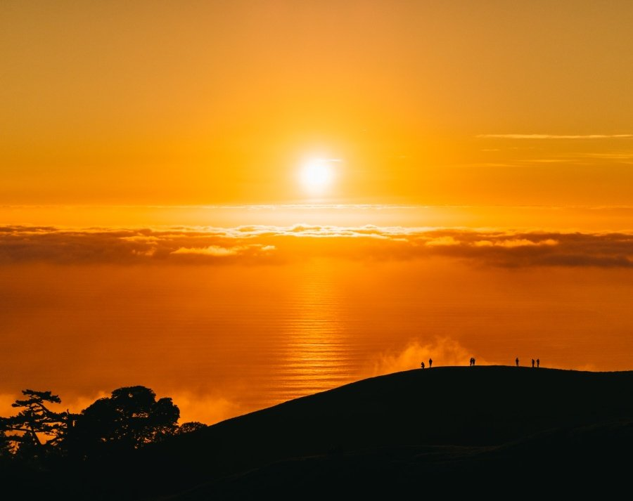 People watching the setting sun atop a mountain to present daylight saving time.