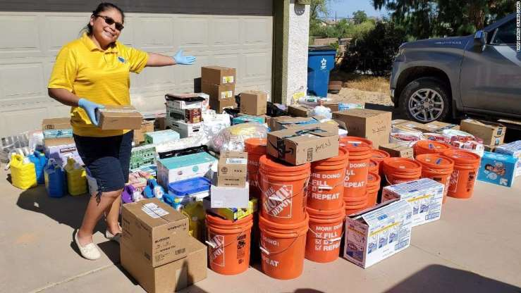 Picture of Theresa Hatathlie smiling next to sewing and hygiene supplies donated by the Auntie Sewing Squad.
