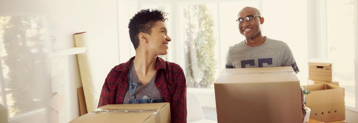 Picture of a couple with moving boxes to represent near, far, wherever find out who's moving to your town