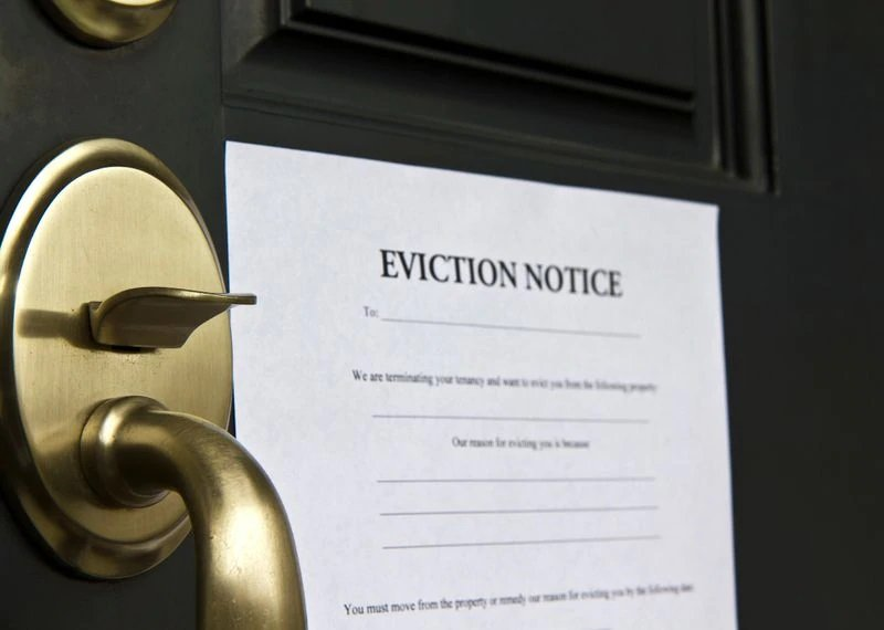 Picture of a door with an eviction notice posted on it