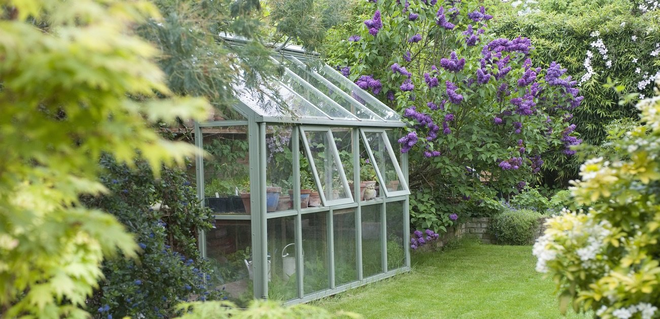 Picture of a greenhouse in a back yard representing Greenhouses Grow in Demand as Gardening Takes Off