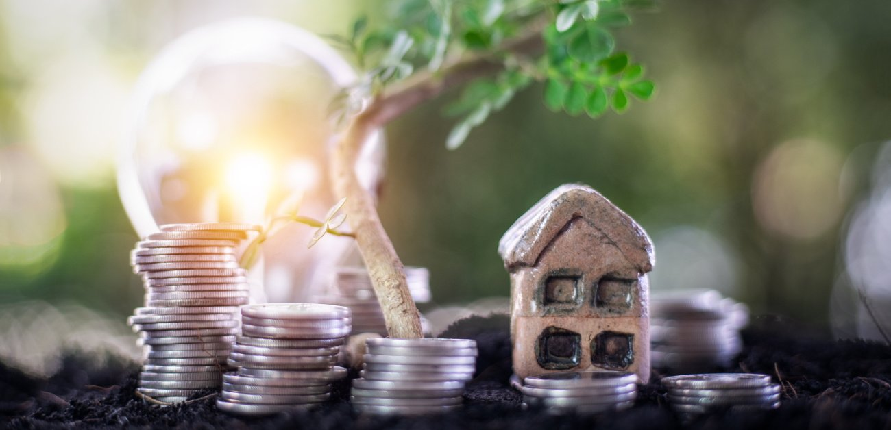 Picture of a lightbulb and a house with decreasing sized piles of coins representing Where to Find Deepest Seasonal Discounts on Homes