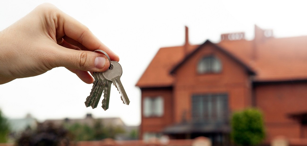 Picture of a persons hand holding keys to a home with a home in the background to representing the 2021 rental market.