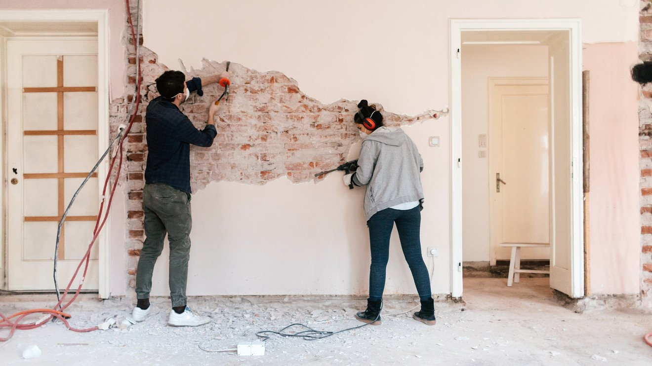 Remodeling Trenda - A Man and a Woman work on stipping a wall of plaster as part of a remodeling project.