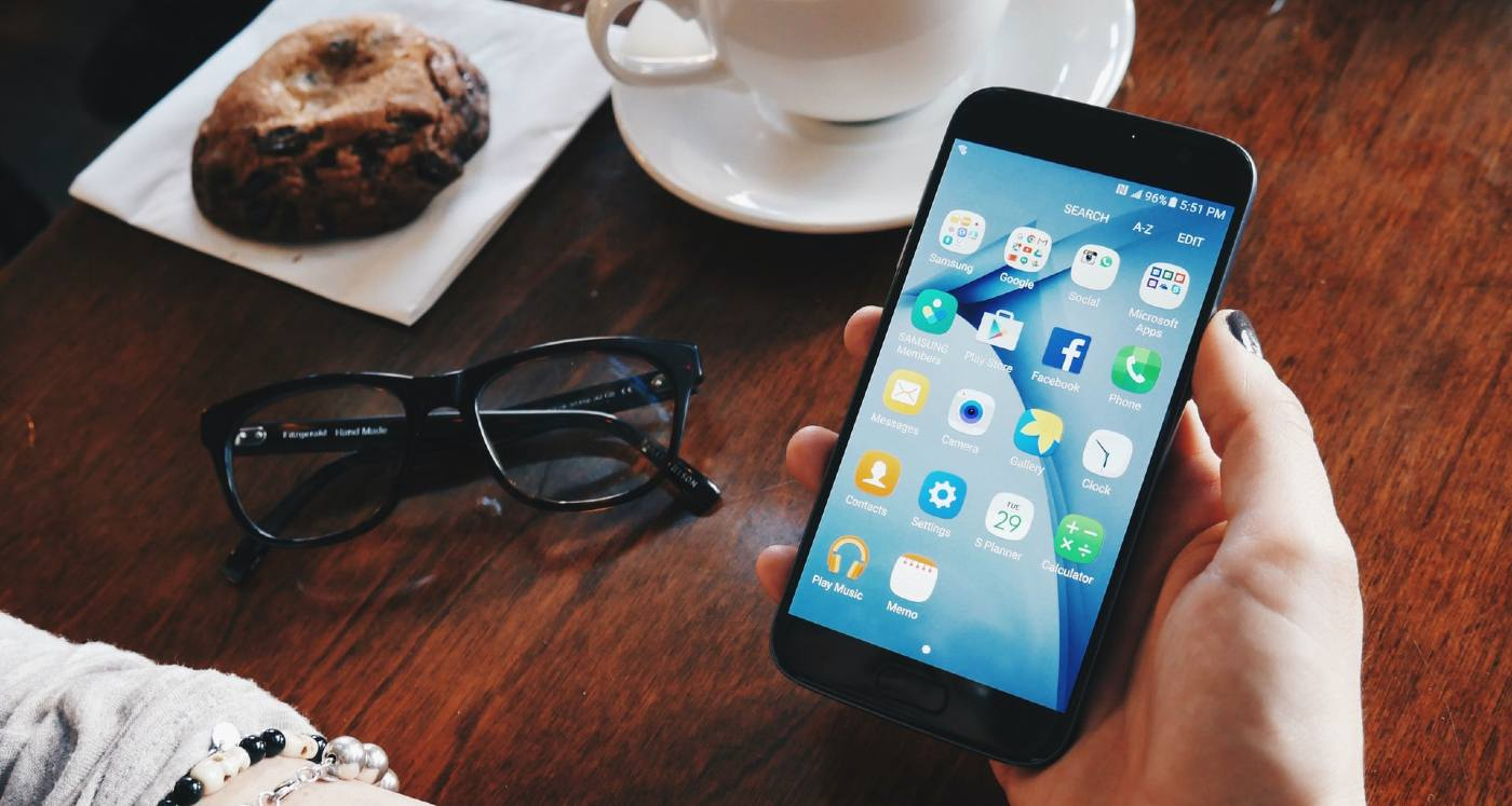 Smart Technology is Not Making Us Dumber After All, According to New Study - Picture of a hand holding a smartphone at a table with various items on the table.