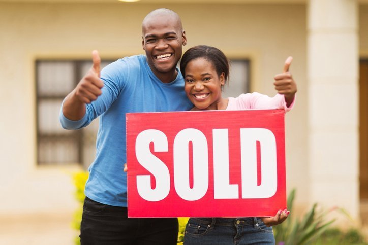 Happy Couple with man giving thumbs up sign while woman is holding a Sold sign.