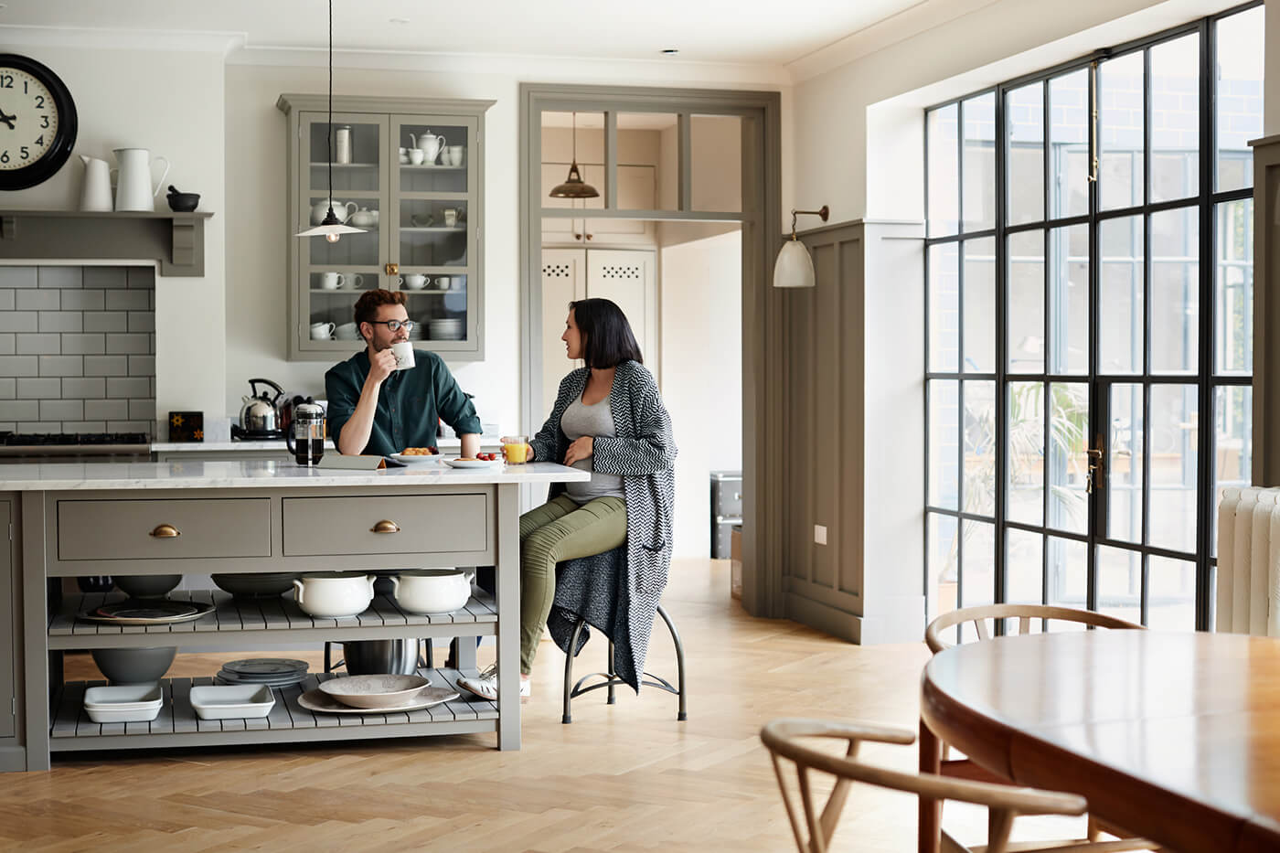 a man and woman eating breakfast in the kitchen