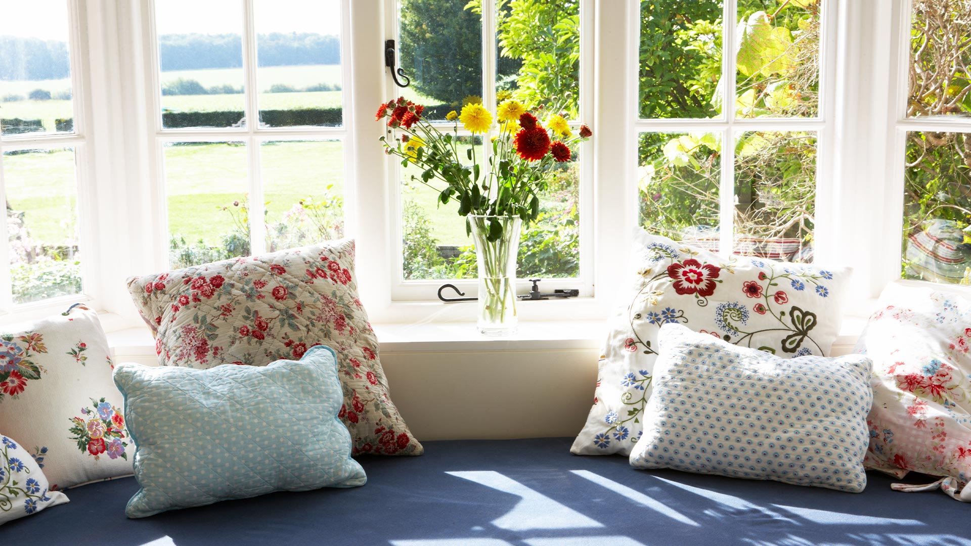 Picture of a lovely window seat and a window looking at flowers, bushes and a field.