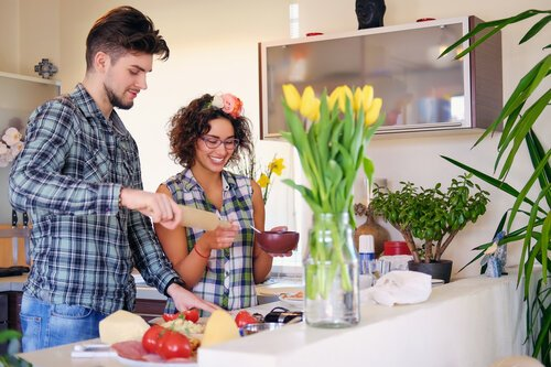 Couple of brunette female and a male in fleece shirt cooking the food in a home family kitchen.