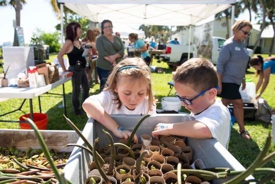 A young girl and boy looking at growing plants with people in the background setting up their tents for a festival.