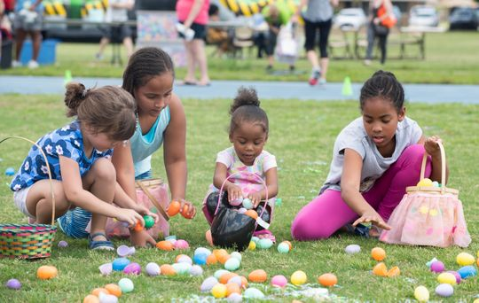 Children collecting Easter Eggs in a Easter Egg lawn Hunt