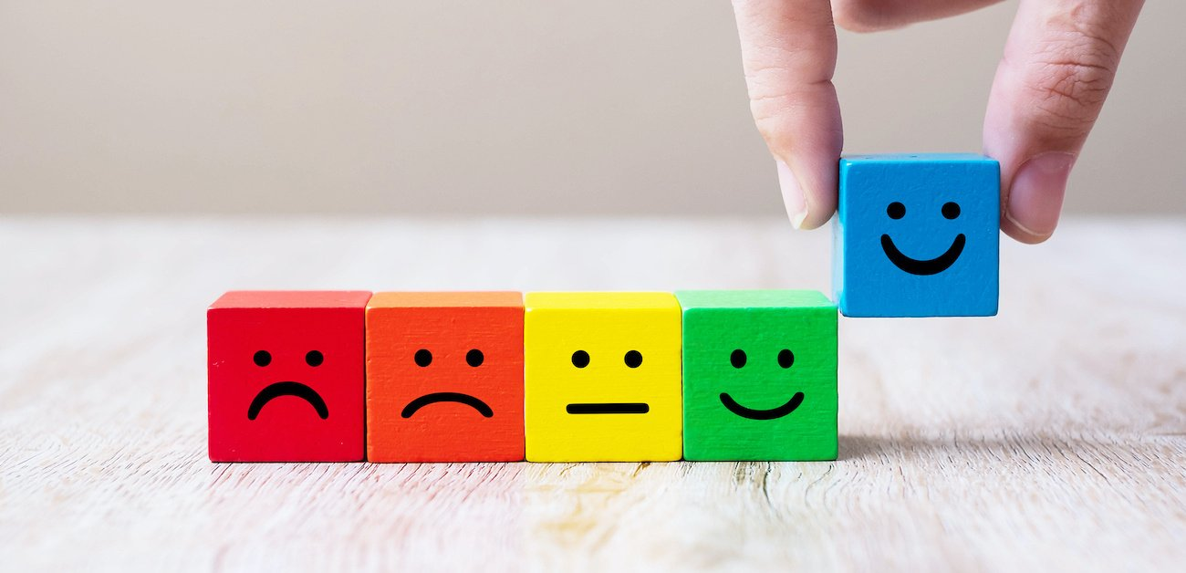 colorful blocks with faces from mad, sad, meh to happy representing what's holding back your marketing.