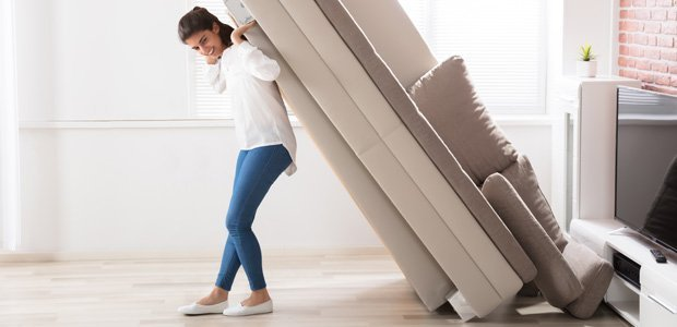 A woman lift up a sofa against her back.