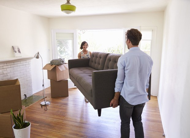 A man and a woman lifting a sofa to put it in their new living room..