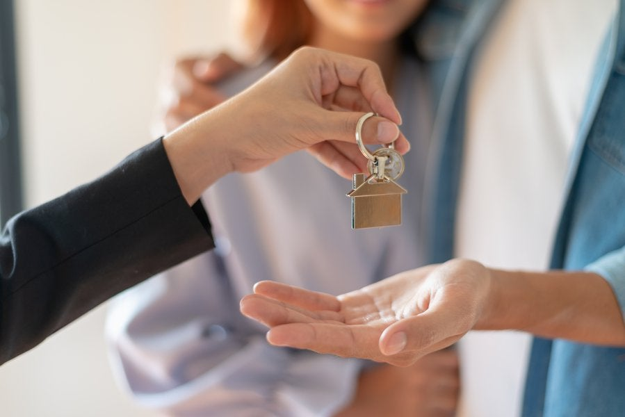 A woman handing a couple keys to their new home.