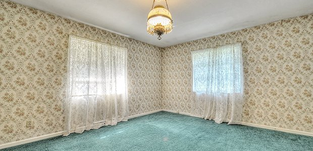 Picture of a room showing outdated wall paper, carpeting and drapes.