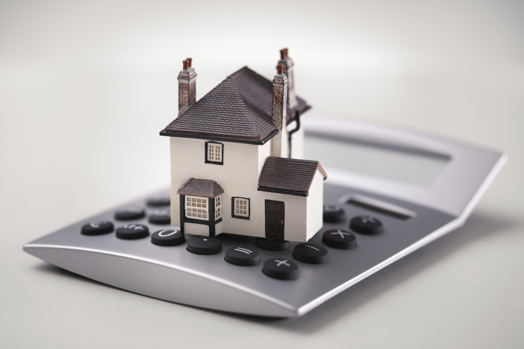 Picture of a toy house sitting on a calculator.