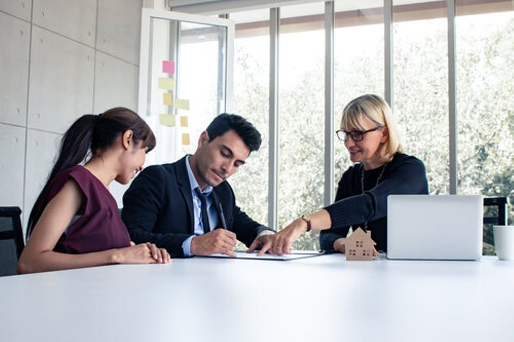 A man and woman consult with a realtor on a sales contract representing Homes less overpriced in July